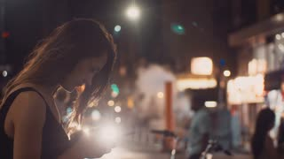 Portrait of young happy woman standing in the evening in crowded downtown and using the smartphone in New York, America.