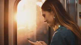 Portrait of young happy woman taking a subway in Chicago, USA. Smiling female using smartphone on sunset.