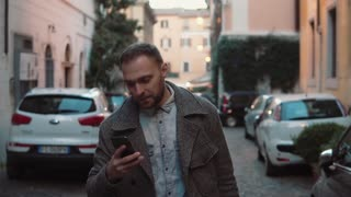 Portrait of young man walking in the evening city with smartphone. Handsome male texting with touchscreen. Slow motion.