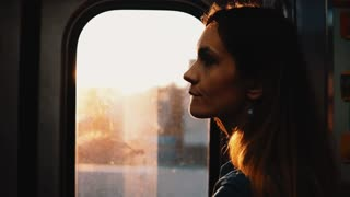 Portrait of young pensive woman taking subway in Chicago, America on sunset. Sad female inside of moving train.