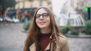 Portrait of young smiling student in glasses looking at camera and drinking tea. Happy woman walking in Paris, France.