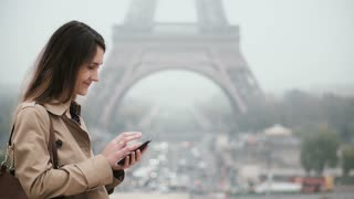 Portrait of young stylish woman standing in the downtown near the Eiffel tower in Paris, France and using smartphone.