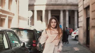 Portrait of young stylish woman walking in the city centre. Inspired and happy girl explores the old streets of the city