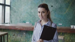Portrait of young successful caucasian woman looking at camera and smiling. Female holds the documents at modern office.