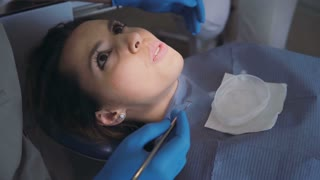 Portrait of young woman visiting dentist. Female sitting in dental chair and talking. Girl touches teeth with tongue.