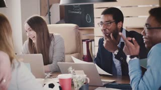 Positive African American male CEO laughs at multiethnic office team meeting by the table in loft coworking slow motion.