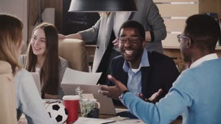 Positive African American male team leader laughs at multiethnic office team business meeting discussion slow motion.
