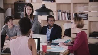 Positive female business coach gives directions to multiethnic team. Young woman boss leads office meeting slow motion.