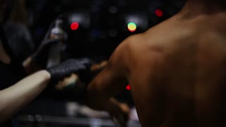 Preparing for bodybuilding competitions. Hands spreading tan cream using a sponge on womans back and shoulders. Backview