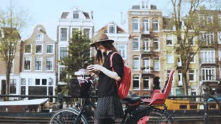 Pretty 30s lady with bike types message on bridge. Creative fashionable art worker on a picturesque old town bridge. 4K