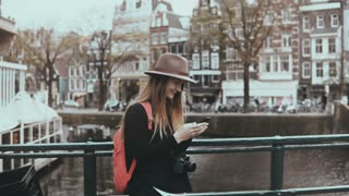 Pretty lady uses social networks on smartphone. 4K. Adult 30s European female with long hair in hat types a message.
