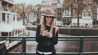 Pretty woman using smartphone on a bridge. 4K. Young lady in stylish hat with long hair and camera types a message.