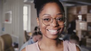 Pretty young African American happy female leader in glasses smiling at camera in modern office co-working background 4K