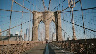 Romantic couple spin and dance at Brooklyn Bridge on a beautiful summer day. Happiness, relationship and love concept 4K