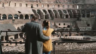 ROME, ITALY-11. 02. 2017 Back view of young couple standing inside the Colosseum and enjoying the scenic view of ruins.