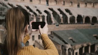 ROME, ITALY-11. 02. 2017 Young woman standing inside the Colosseum and taking photos on smartphone, enjoying the view.