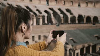 ROME, ITALY-11. 02. 2017 Young woman standing inside the Colosseum in Rome and taking photos of ruins on smartphone.