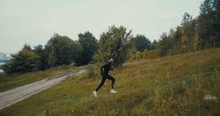 Runner going fast uphill on a cross country path. Drone side view. Concentrated athlete sportsman achieving life goal.