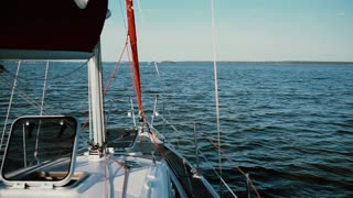Sailboat moving in the lake, splashing water. Yacht breaking the waves with full speed.