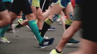 SAINT PETERSBURG RUSSIA, JULY 9 2017 - Side view of legs and feet of running people in different sport shoes slow motion