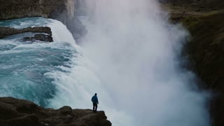 Scenic landscape of the lonely man standing on the edge of the mountain and looking on the Gullfoss waterfall in Iceland