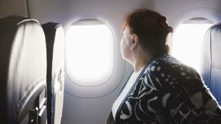 Senior European female airplane passenger sitting on the airplane window seat, nervous and scared to fly, looking around