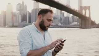 Serious European businessman typing message on smartphone messenger app at amazing New York City sunset scenery 4K.