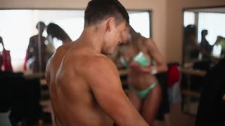 Side, back view of male bodybuilder with bare torso doing exercise with resistance band. Woman in bikini at background