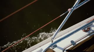 Side of the sailboat goes through the waves with full speed. Sailing in the wind in sunny day. Close-up view.