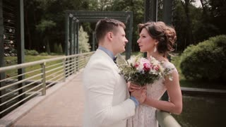 Side view of a beautiful loving couple on their wedding day. Bride in a white wedding dress, groom in a gown on a bridge