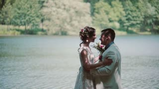 Side view of a kissing couple on their wedding day. Happy bride and groom laugh in a beautiful place on a river bank.