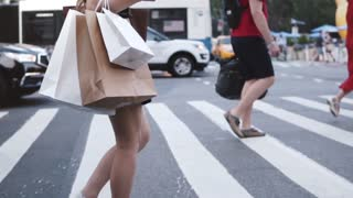 Side view of anonymous young woman carrying shopping bags while crossing the street in New York City slow motion.