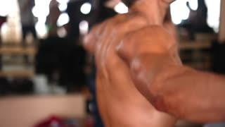 Sideview of a male bodybuilder with bare torso doing exercise with resistance band