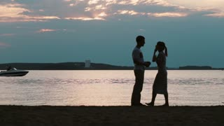 Silhouette of young happy couple talking on the beach. Man and woman walking on sunset, motorboat on the background.