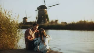 Single dad with two kids sit on a sunny lake pier. Traditional Dutch windmills in Netherlands. Family relationships. 4K.