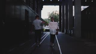 Slow motion back view happy romantic couple walking together holding hands on rails under dark evening city bridge.