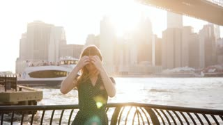 Slow motion beautiful Caucasian young woman posing, touching hair on amazing New York sunset, big boats passing by.
