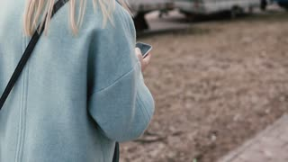 Slow motion blonde woman using social networks. Back view. Girl surfing websites walking autumn street. Lifestyle shot.