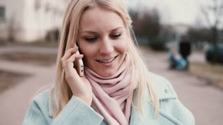 Slow motion Caucasian woman chatting on the phone. Lovely attractive young 20s happy blonde ending call saying goodbye.