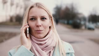 Slow motion Caucasian woman talking on the phone. Lovely stylish beautiful young 20s blonde chatting smiling happily.
