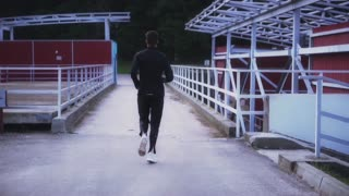 Slow motion. Fit athlete running on small bridge. Background shot. Fitness running in suburban landscape. Back view.
