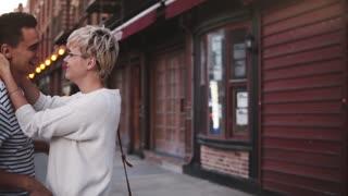 Slow motion happy European girl biting nose of her boyfriend smiling, enjoying walk along New York City evening street.