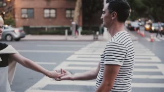 Slow motion happy fun multiethnic couple hugging, dancing and jumping over street pedestrian crossing in New York City.