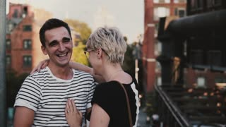 Slow motion happy Hispanic man and European girl talking and laughing together on a big city bridge in summer New York.