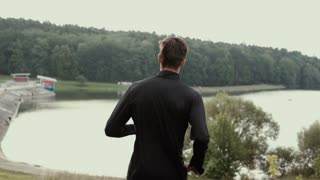 Slow motion. Man running downhill to lake shore. Camera follows young male going down steep hill. Back view background