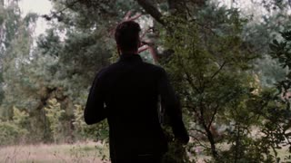 Slow motion. Man running through deep woods. Camera follows young male going out of the forest to scenic lake shore