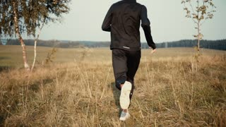 Slow motion. Man running to rolling autumn field. Camera follows runner in beautiful quiet fall background scenery view.