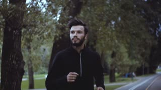Slow motion portrait of Caucasian man running. Close up handsome businessman reflecting and working out in quiet park.