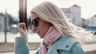 Slow motion portrait of confident pretty woman. Attractive successful Caucasian female smoothing flying hair sunglasses.
