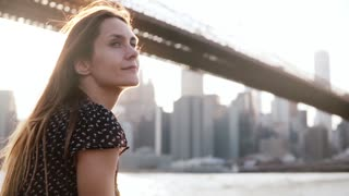 Slow motion portrait of peaceful Caucasian girl with golden hair looking around, enjoying scenic New York sunset view.